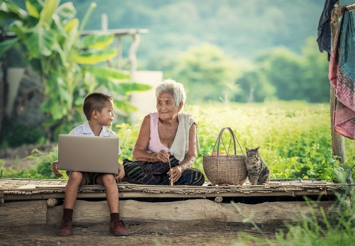 young boy working with laptop in rural area